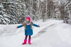 A menina vestiu-se em um revestimento azul e um chapéu cor-de-rosa e botas, hamming e jogo na floresta do inverno Foto de Stock