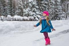 A menina vestiu-se em um revestimento azul e um chapéu cor-de-rosa e as botas, divertimento correm através da floresta do inverno Fotografia de Stock