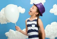 A menina vestiu-se em vestido listrado e no chapéu da cor que levantam em um fundo azul com nuvens do algodão, balão de ar branco fotografia de stock royalty free