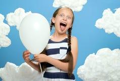 A menina vestiu-se em vestido listrado que levanta em um fundo azul com nuvens do algodão, o balão de ar branco, o conceito do ve foto de stock