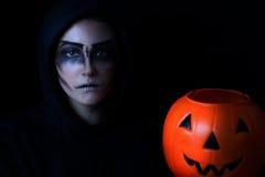 A menina vestiu-se na pintura assustador da cara com a cubeta da abóbora em vagabundos pretos fotos de stock royalty free