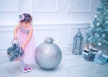 A menina vestiu-se no vestido bonito da flor branca da forma que levanta perto da árvore de Natal Fotografia de Stock