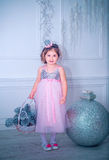A menina vestiu-se no vestido bonito da flor branca da forma que levanta perto da árvore de Natal Imagem de Stock Royalty Free