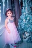 A menina vestiu-se no vestido bonito da flor branca da forma que levanta perto da árvore de Natal Foto de Stock Royalty Free