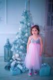 A menina vestiu-se no vestido bonito da flor branca da forma que levanta perto da árvore de Natal Imagens de Stock Royalty Free