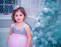 A menina vestiu-se no vestido bonito da flor branca da forma que levanta perto da árvore de Natal Foto de Stock
