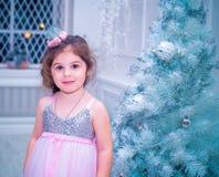 A menina vestiu-se no vestido bonito da flor branca da forma que levanta perto da árvore de Natal Imagens de Stock