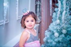 A menina vestiu-se no vestido bonito da flor branca da forma que levanta perto da árvore de Natal Fotos de Stock