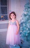 A menina vestiu-se no vestido bonito da flor branca da forma que levanta perto da árvore de Natal Fotografia de Stock Royalty Free