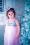 A menina vestiu-se no vestido bonito da flor branca da forma que levanta perto da árvore de Natal Fotos de Stock Royalty Free