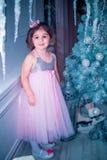 A menina vestiu-se no vestido bonito da flor branca da forma que levanta perto da árvore de Natal Imagem de Stock