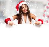 A menina vestiu-se para o Natal que mostra uma placa vazia fotografia de stock royalty free