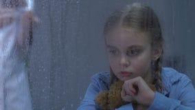 Menina virada pequena que grita e que abraça o urso de peluche, enfermeira que prepara a injeção, cura vídeos de arquivo