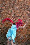 A menina voa em uma parede de tijolo Foto de Stock Royalty Free