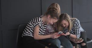 Meninas adolescentes alegres que apreciam o índice dos meios no telefone celular