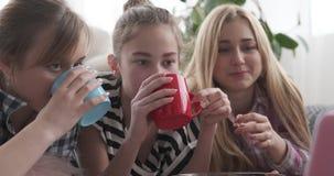 Meninas adolescentes que comem a pipoca ao olhar o índice dos meios no portátil video estoque