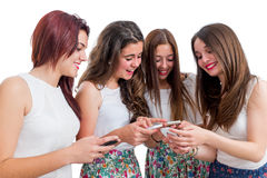 Meninas adolescentes que compartilham da informação em telefones espertos Imagens de Stock