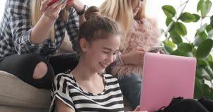 Meninas adolescentes que consultam seu índice social dos meios no portátil e nos telefones celulares