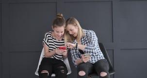 Meninas adolescentes que discutem o quando usando o app social dos meios em telefones celulares