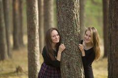 Meninas adolescentes que estão em uma floresta perto da árvore nave Foto de Stock Royalty Free