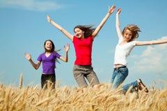 Meninas adolescentes que saltam em um campo de trigo Fotografia de Stock Royalty Free