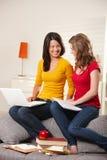 Meninas adolescentes que sorriem no sofá em casa Imagem de Stock Royalty Free