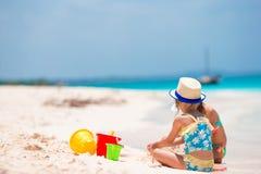 Meninas adoráveis durante férias de verão As crianças que jogam com praia brincam na praia branca foto de stock