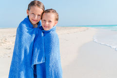 Meninas adoráveis envolvidas na toalha na praia tropical após nadar no mar Fotos de Stock Royalty Free