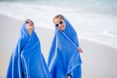 Meninas adoráveis envolvidas na toalha na praia tropical após nadar no mar Duas irmãs que jogam na praia Imagens de Stock