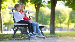 Meninas adoráveis pequenas com o smartphone na queda Crianças que têm o divertimento no dia ensolarado morno do outono fora vídeos de arquivo