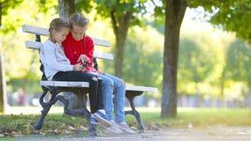 Meninas adoráveis pequenas com o smartphone na queda Crianças que têm o divertimento no dia ensolarado morno do outono fora video estoque