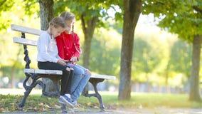 Meninas adoráveis pequenas com o smartphone na queda fora Crianças que têm o divertimento no dia ensolarado morno no parque do ou filme
