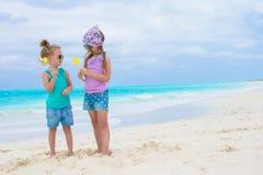 Meninas adoráveis pequenas com os ovos na praia tropical branca Imagens de Stock