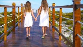 Meninas adoráveis pequenas em uma ponte de madeira em sua maneira a um oceano tropical branco da praia e da turquesa video estoque