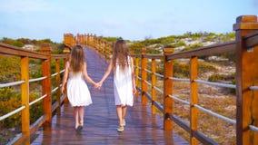 Meninas adoráveis pequenas em uma ponte de madeira em sua maneira a uma praia tropical branca vídeos de arquivo