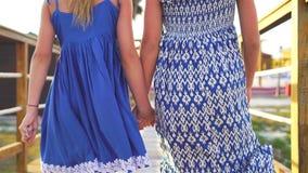 Meninas adoráveis pequenas em uma ponte de madeira na praia tropical branca Mãos do close up das crianças que guardam-se filme