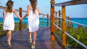 Meninas adoráveis pequenas em uma ponte de madeira que corre à praia em férias luxuosas filme