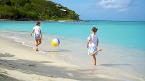 Meninas adoráveis pequenas que jogam com a bola do ar na praia As crianças felizes apreciam férias filme