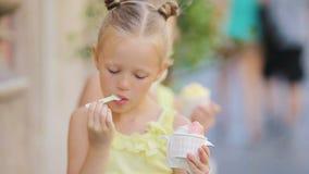 Meninas adoráveis que comem o gelado fora no verão Crianças bonitos que apreciam o gelato italiano real perto de Gelateria em Rom video estoque