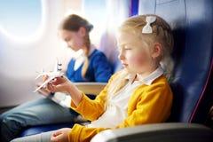 Meninas adoráveis que viajam por um avião Crianças que sentam-se pela janela dos aviões e que jogam com plano do brinquedo foto de stock