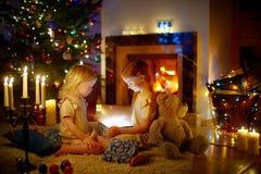 Meninas adoráveis que abrem um presente mágico do Natal Imagem de Stock