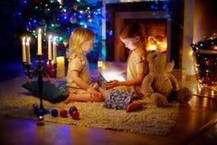 Meninas adoráveis que abrem um presente mágico do Natal Fotografia de Stock
