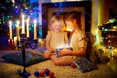 Meninas adoráveis que abrem um presente mágico do Natal Fotografia de Stock Royalty Free