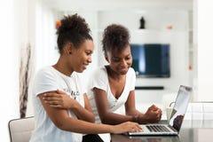 Meninas afro-americanos do estudante que usam um laptop - p preto