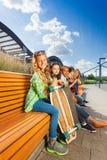 Meninas agradáveis que sentam-se no banco de madeira no estilo urbano Fotos de Stock Royalty Free