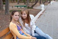Meninas alegres do estudante que sentam-se no banco Imagens de Stock Royalty Free