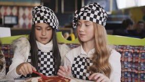 Meninas alegres no uniforme que cozinham uma pizza, na classe mestra de chefe no café filme