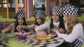 Meninas alegres no uniforme que cozinham uma pizza na classe mestra de chefe no café 4K vídeos de arquivo