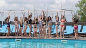 Meninas alegres nos maiôs que saltam perto da piscina, vida do verão da juventude no fim de semana, amigas de cabelos compridos d