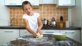 Meninas alegres novas que amassam a massa na tabela escura na cozinha video estoque
